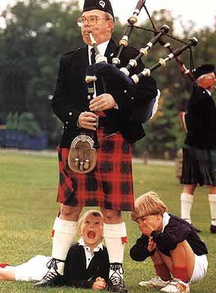 photo of bagpiper and curious children